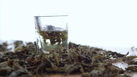 Tea leaf dissolving in hot water on white background Footage
