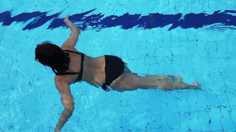 slowmotion of a attractive woman swimming in the pool Footage
