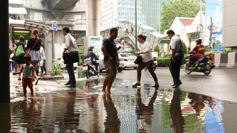 Group Of People Cross Puddle After Rain On Road, Going To Sidewalk From Roadway stock footage