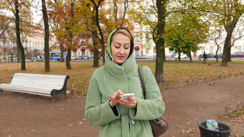 Young Woman Walk With Smartphone In Autumn Park, Answer Phone Call stock footage