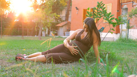 Happy Pregnant Woman In Garden At Sunset stock footage
