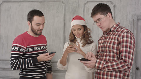 Three Friends Use Their Cell Phones On A White Background stock footage