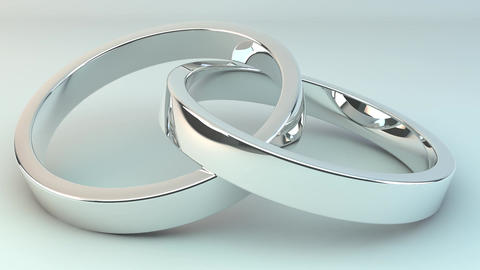 Wedding rings joined together against a white background Footage