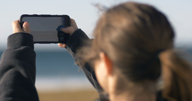 Woman Taking Photographs Using Mobile Cell Phone Camera stock footage