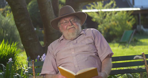 Retired elderly man relaxing outdoors reading a book enjoying retirement Footage